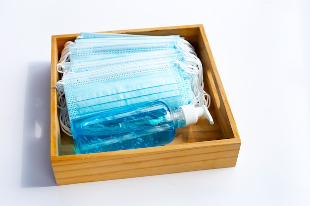 Gesichtsmasken mit alkohol flüssigem gel-desinfektionsmittel in holzkiste auf weißer oberfläche