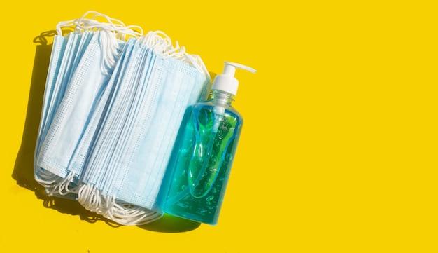 Gesichtsmasken mit flüssigem gel-desinfektionsmittel für alkohol auf gelber oberfläche