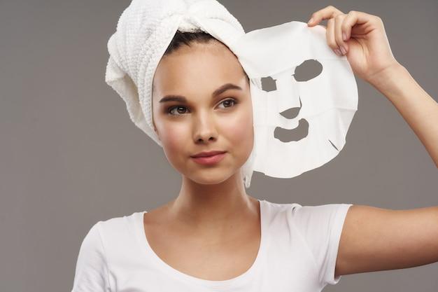 Gesichtsmaskenhandtuch auf dem kopf eines schönen mädchens