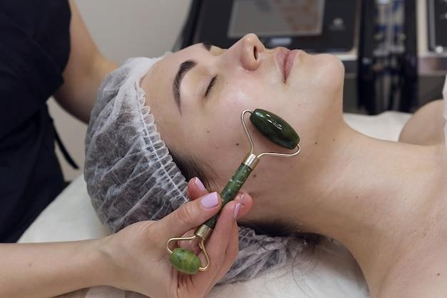 Gesichtsmassage im schönheitssalon, jade facial massage roller.