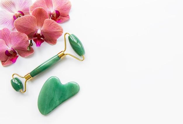 Gesichtsmassage-jadewalzen und orchideenblumen auf weißem hintergrund