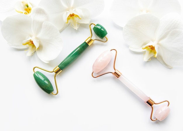 Gesichtsmassage-jadewalzen und orchideenblumen auf weißem tisch