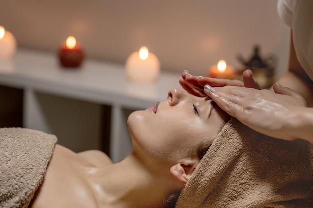 Gesichtsmassage nahaufnahme der jungen frau, die spa-massagebehandlung erhält