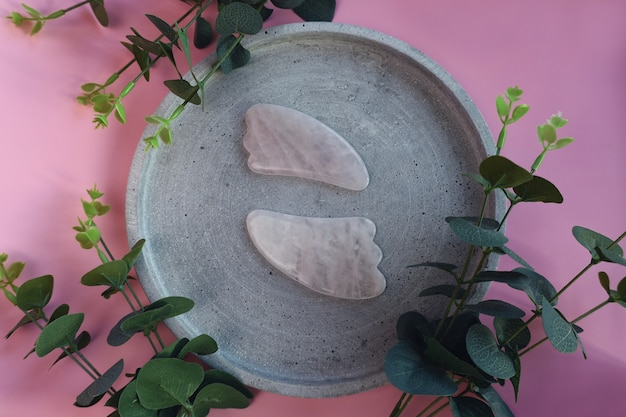 Gesichtsmassage-set. gesichtsroller und gua-sha-massagegerät aus natürlichen rosa steinen, wohlbefinden, gesichts-fitness-konzept, stilvolle monochrome karte, luxusbanner.