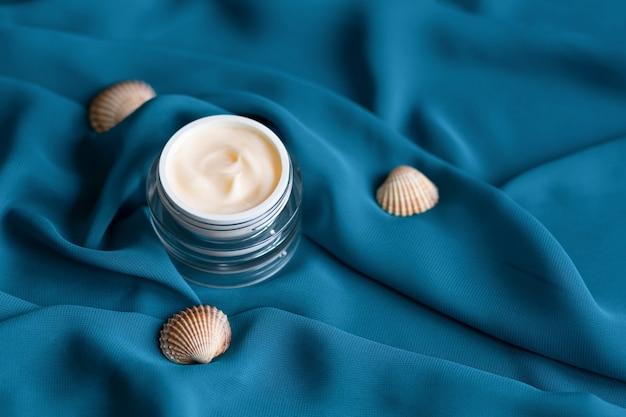 Gesichtsmineral-feuchtigkeitscreme mit muscheln im glas auf blauer seide.