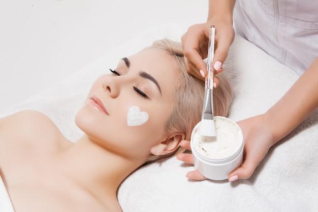 Gesichtspeeling-maske, spa-beauty-behandlung, hautpflege. frau, die gesichtspflege durch kosmetikerin am badekurortsalon erhält. vorbildliches lügen auf couch mit geschlossenen augen. kosmetologische klinik. gesundheitswesen, klinik, kosmetologie