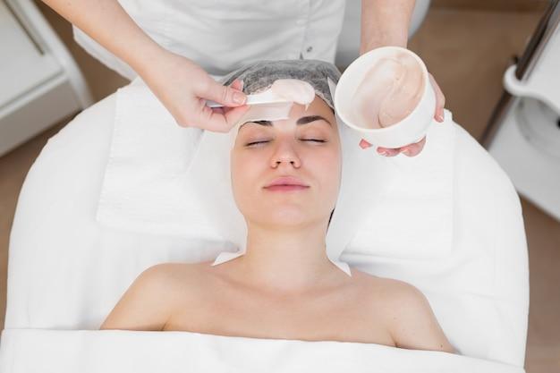 Gesichtspeeling-maske, spa-schönheitsbehandlung, hautpflege. frau, die gesichtspflege durch kosmetikerin am spa-salon erhält. frau macht eine alginatmaske. mädchen mit einer maske aus beigem ton