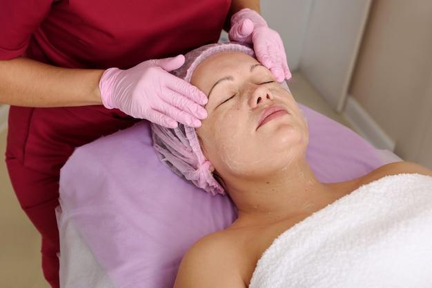 Gesichtspeeling-maske, spa-schönheitsbehandlung, hautpflege. frau, die gesichtspflege durch kosmetikerin am spa-salon erhält