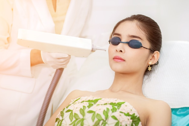 Gesichtspflege. gesichts-laser-haarentfernung. kosmetiker, der laser epilation treatment young gibt