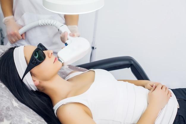 Gesichtspflege. gesichtslaser-haarentfernung. kosmetiker, der dem gesicht der jungen frau an der schönheits-klinik laser-epilierungs-behandlung gibt. körperpflege. haarlose glatte und weiche haut. gesundheits- und schönheitskonzept.