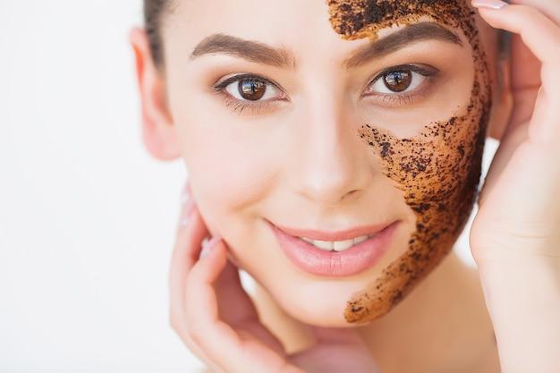 Gesichtspflege. junges charmantes mädchen macht eine schwarze holzkohle-maske auf ihrem gesicht