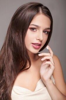Gesichtspflege. porträt der sexy jungen frau mit tropfen der kosmetischen creme auf haut unter augen