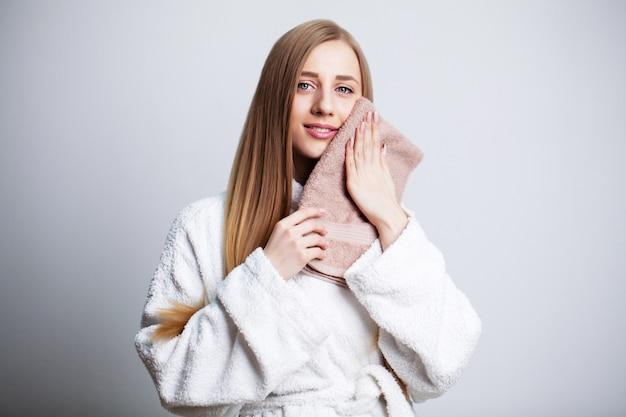 Gesichtspflege, schöne frau wischt ihr gesicht mit einem handtuch nach dem duschen.