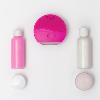 Gesichtspflege. silikongesichtsbürste, reiniger und waschendes gel, natürliche kosmetische creme auf papierhintergrund mit kopienraum. tiefenreinigung der haut. flach liegen. ansicht von oben.