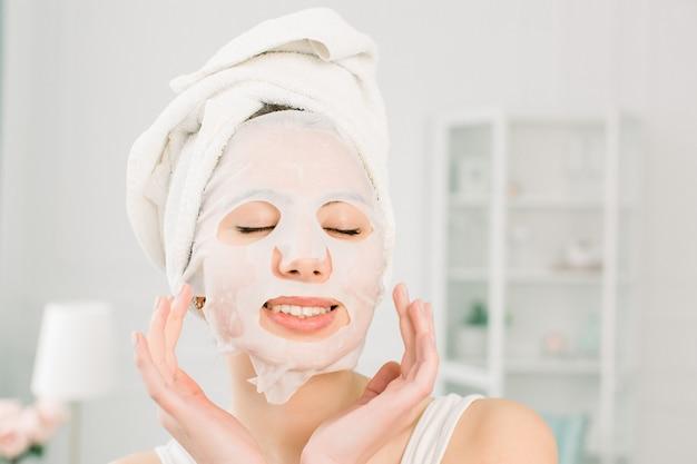 Gesichtspflege und schönheitsbehandlungen. frau im weißen handtuch mit einer feuchtigkeitsspendenden stoffmaske auf ihrem gesicht, die ihre augen schließt, lokalisiert auf hellem raum