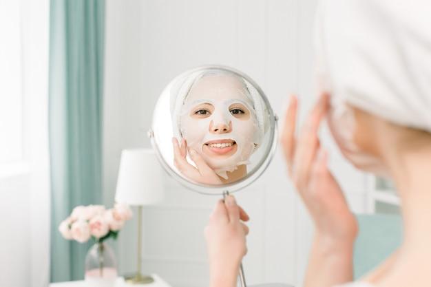 Gesichtspflege und schönheitsbehandlungen. frau mit einer feuchtigkeitsspendenden lakenmaske auf ihrem gesicht und einem weißen handtuch auf dem kopf, das den spiegel betrachtet.