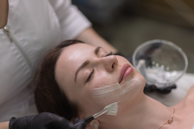 Gesichtspflege und schutz. eine junge frau bei einer kosmetikerin. der spezialist trägt eine crememaske auf das gesicht auf.