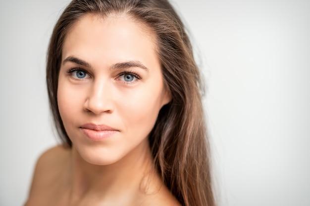 Gesichtsporträt der jungen kaukasischen frau mit natürlichem make-up und wimpernverlängerungen, die kamera auf weißem hintergrund betrachten