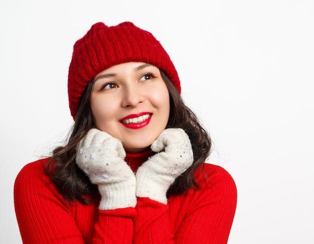 Gesichtsporträt der niedlichen glücklichen jungen frau in der roten strickmütze und im pullover auf weiß.