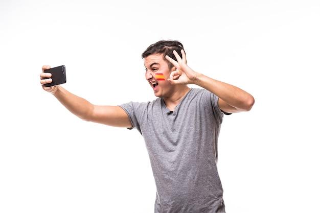 Gesichtsporträt von spanien fußballfan nehmen selfie auf weißem hintergrund. fußballfans konzept.