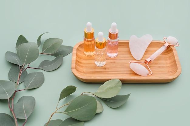 Gesichtsrollen, ätherische öle oder kosmetische seren mit natürlichen eukalyptusblättern auf mintgrünem hintergrund