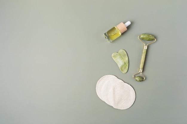Gesichtsroller aus grüner jade, gua-sha-stein, ätherisches öl. natürliches hautpflegekonzept. ansicht von oben, flach