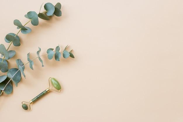 Gesichtsroller massagetherapie. grünes jadestein-gesichtsrollenmassagegerät mit eukalyptusblättern auf hellbeigem hintergrund. flache lage, kopienraum, ansicht von oben. feminine entspannte atmosphäre.