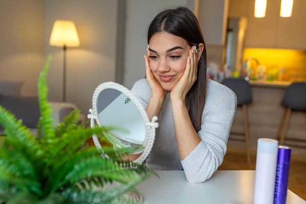 Gesichtsschönheit. porträt der sexy jungen frau mit der frischen gesunden haut, die zuhause im spiegel schaut