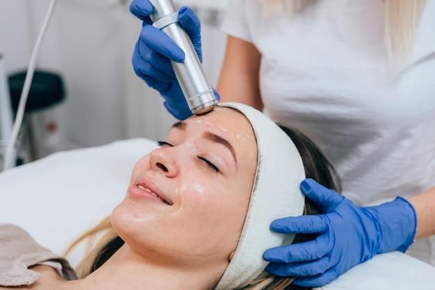Gesichtsschönheitsbehandlung der schönen jungen frau mit sauerstoff im kosmetischen schönheitssalon.