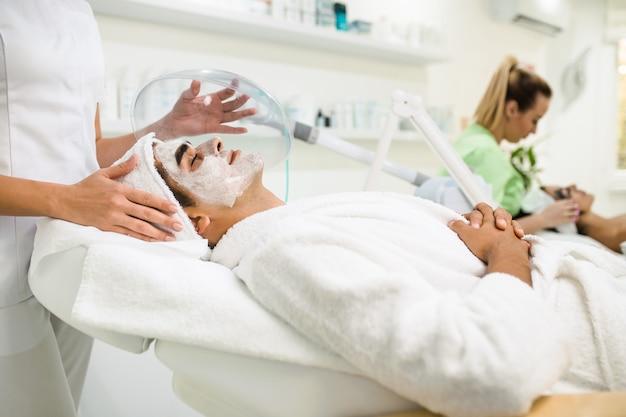 Gesichtsschönheitsbehandlung eines gut aussehenden mannes mit sauerstoffmaske im kosmetischen schönheitssalon.