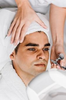 Gesichtsschönheitsbehandlung eines gutaussehenden mannes mit sauerstoff-epidermispeeling im kosmetischen schönheitssalon.