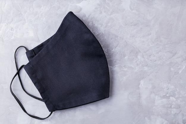Gesichtsschutzmaske auf ultimativem grauem hintergrund. antivirenmaske aus schwarzer baumwolle. speicherplatz kopieren