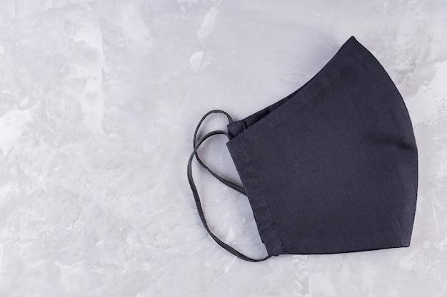Gesichtsschutzmaske auf ultimativem grauem hintergrund. antivirenmaske aus schwarzer baumwolle.
