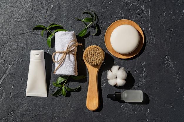 Gesichtsserum, creme, massagebürste und seifenstück mit weißem handtuch und baumwollblume auf schwarzem hintergrund. bio-kosmetik. behandlung spa schönheit hautpflege, gesundheitswesen. markenwerbung. produktfoto.