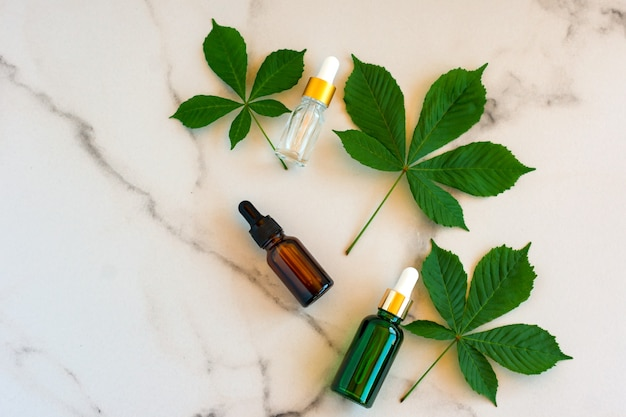 Gesichtsserum in glasflaschen mit pipette, grüne blätter auf marmorhintergrund. blanko-etikettenpaket für das branding-mock-up. frühlingskosmetikkonzept. natürliches bio-schönheitsprodukt.