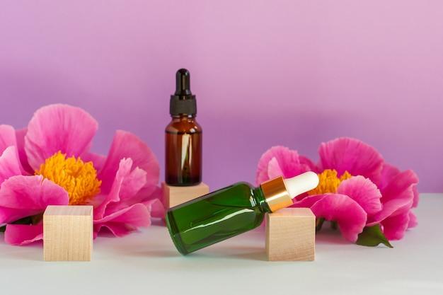 Gesichtsserum in glasflaschen mit pipette, pfingstrosenblüten auf rosa hintergrund. blanko-etikettenpaket für das branding-mock-up. frühlingskosmetikkonzept. natürliches bio-schönheitsprodukt.