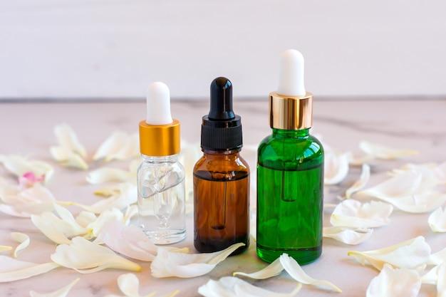 Gesichtsserum in glasflaschen mit pipette, poenieblüten auf marmorhintergrund. blanko-etikettenpaket für das branding-mock-up. frühlingskosmetikkonzept. natürliches bio-schönheitsprodukt.
