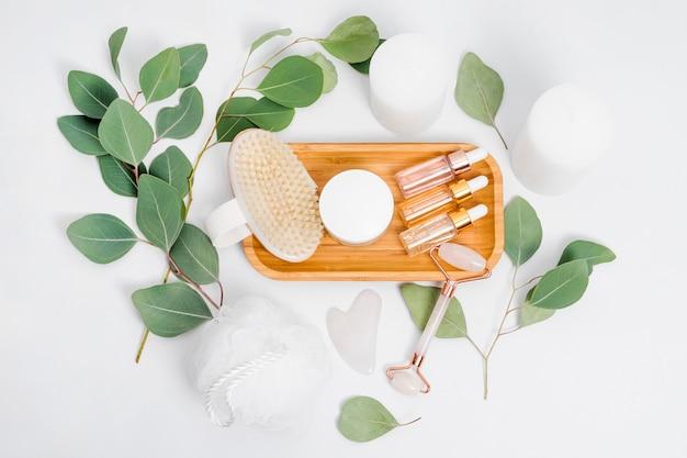 Gesichtswalze, ätherische öle, kosmetische seren, massagepinsel und kerzen mit natürlichen eukalyptusblättern.