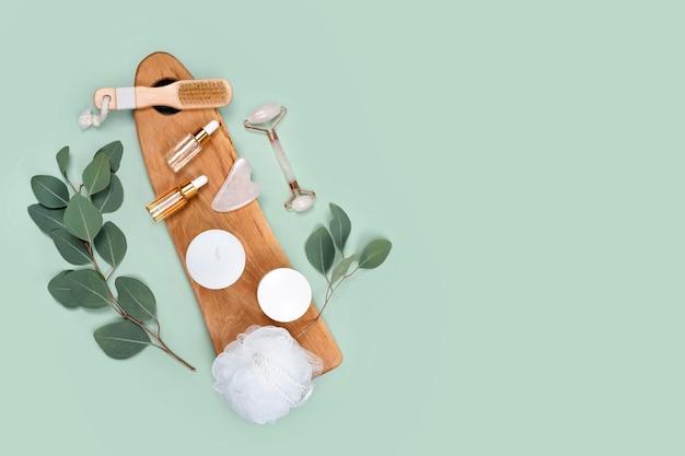 Gesichtswalze, ätherische öle, kosmetische seren, massagepinsel und kerzen mit natürlichen eukalyptusblättern