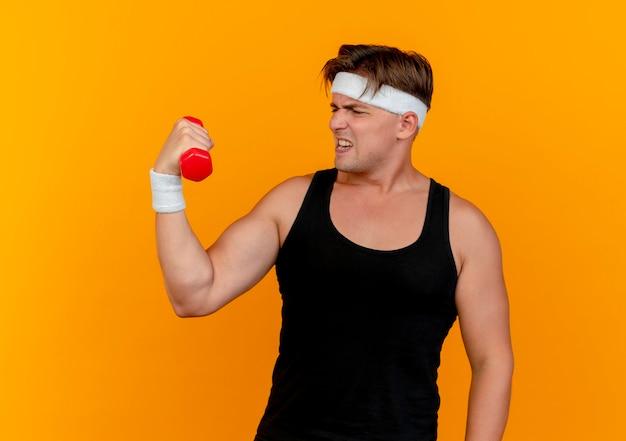 Gespannter junger gutaussehender sportlicher mann, der stirnband und armbänder hält und hantel lokalisiert auf orange wand hält
