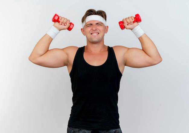 Gespannter junger gutaussehender sportlicher mann, der stirnband und armbänder trägt, die kurzhanteln lokalisiert auf weißer wand heben
