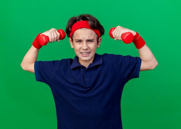 Gespannter junger hübscher sportlicher junge, der stirnband und armbänder mit zahnspangen trägt, die front betrachten, die hanteln lokalisiert auf grüner wand anheben