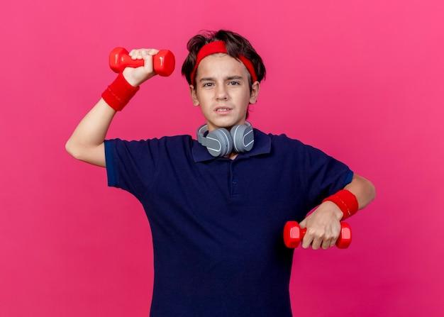 Gespannter junger hübscher sportlicher junge, der stirnband und armbänder und kopfhörer am hals mit zahnspangen trägt, die kamera betrachten, die hantel lokalisiert auf purpurrotem hintergrund anhebt