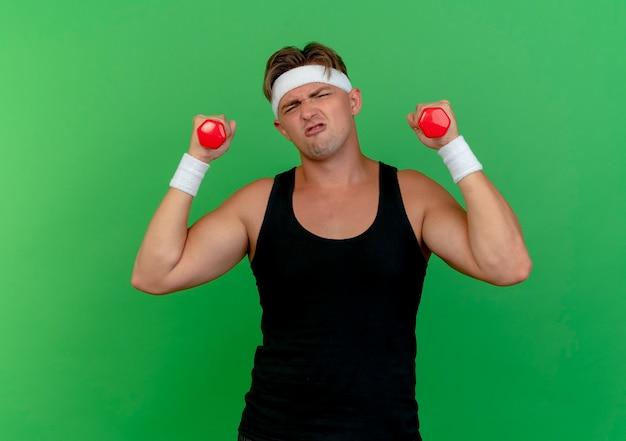 Gespannter junger hübscher sportlicher mann, der stirnband und armbänder trägt, die kurzhanteln lokalisiert auf grüner wand heben