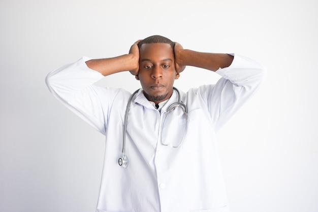 Gespannter schwarzer männlicher doktor, der kopf erfasst. betonter arzt konzept.