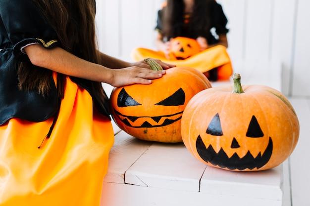 Gespenstische gemalte halloween-kürbise mit kleinen hexen