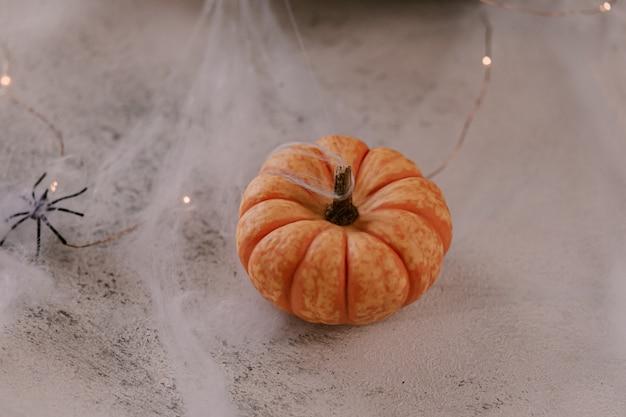 Gespenstische halloween-dekoration mit verschiedenen kürbisen, licht, spinnen.