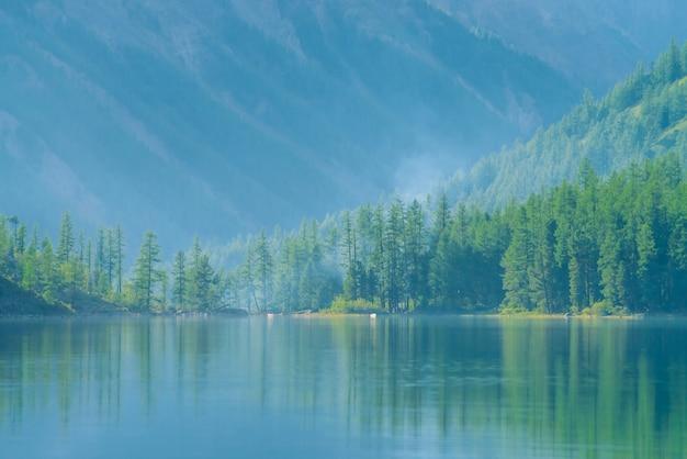 Gespenstischer gebirgssee im hochland am frühen morgen. schöne nebelhafte berge reflektierten sich in der ruhigen klaren wasseroberfläche. rauch von lagerfeuern. erstaunliche atmosphärische neblige landschaft der majestätischen natur.