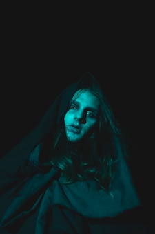 Gespenstischer mann, der kamera in der dunkelheit betrachtet