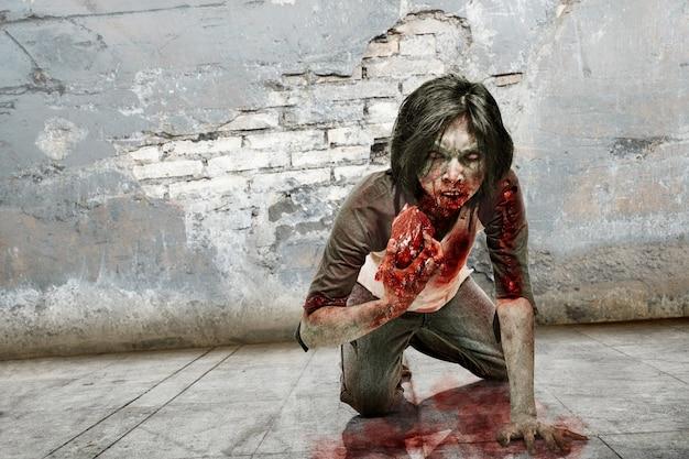 Gespenstischer zombiemann, der das rohe fleisch isst
